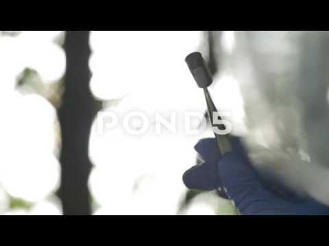 075643355 Forensic Officer Examining 9mm Bullet Shell