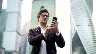 Smiling Businessman in Glasses Using Smartphone in Moscow City | Stock Footage - Videohive