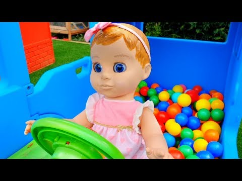Funny Baby Doll Playing with Lots of Balls on the Little Bus