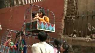 Cute children celebrate Eid festival with small ferris wheel rides