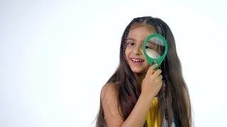 Beautiful young kid happily playing with a magnifying glass against the white background - India