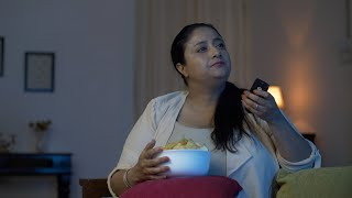 Overweight Indian woman taking handfull of chips and eating in front of a television - Junk food concept