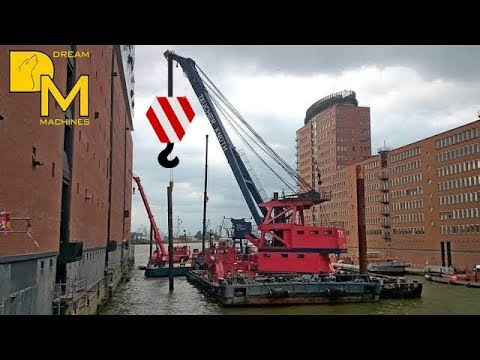 GIANT SHIP CRANE LIFTING STEEL BEAMS ON FLOATING BARGE