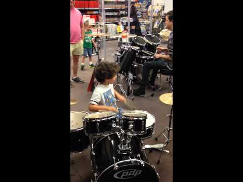 child playing drums with music store employee