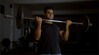 A muscular and fit Indian man doing barbell curl (bicep) exercise in the gym