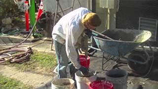 Mixing stucco in a wheelbarrow then installing it