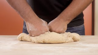 Close up shot of a man kneading dough of wheat flour