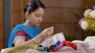 An Indian women / female embroidering at home