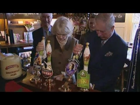 Prince Charles and Camillia pull pints in a pub