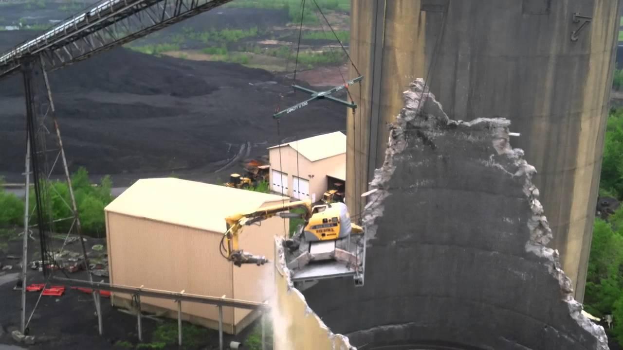 3 Silo Demolition : Brokk attached to t crane demolishing concrete silo