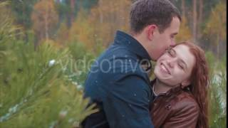 Two Lovers Kissing During Snowfall in Forest