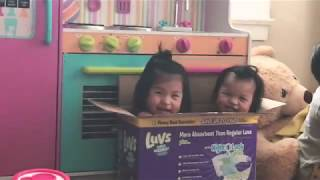 Cute sisters playing and laughing at each other in a diaper box