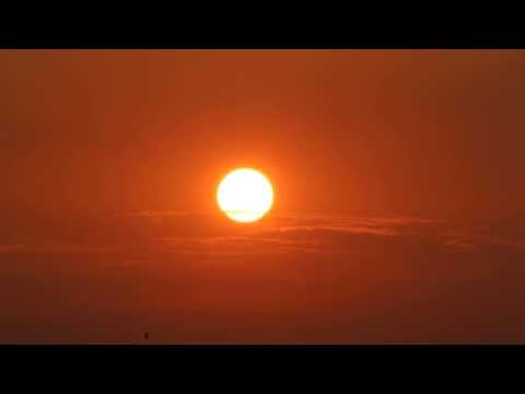 Sun rising reddish with transparent clouds but dropping HD v