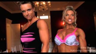 two fitness women compare and measure their big muscles