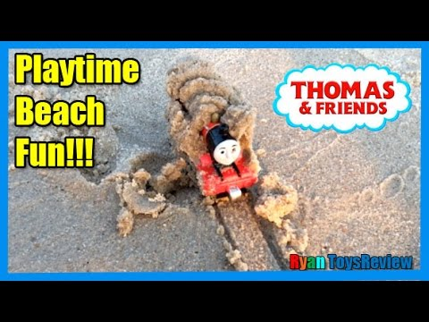 Ryan plays with THOMAS AND FRIENDS on the sand