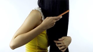 Slow-motion shot of a young female model combing her beautiful straight hair - Hair Care