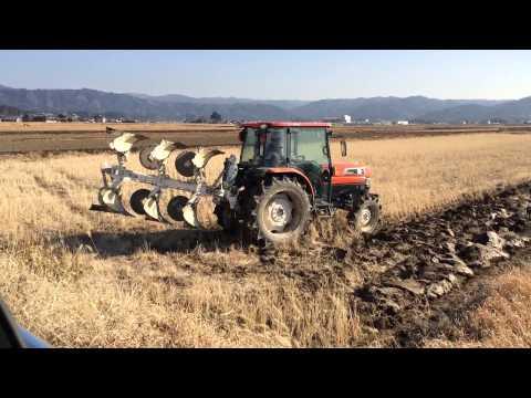 Kubota KL550 ploughing a rice field in Japan. Japán traktor váltva forgató ekével dolgozik.