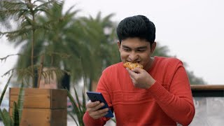 Handsome Indian boy eating delicious pizza and using his smartphone at the same time