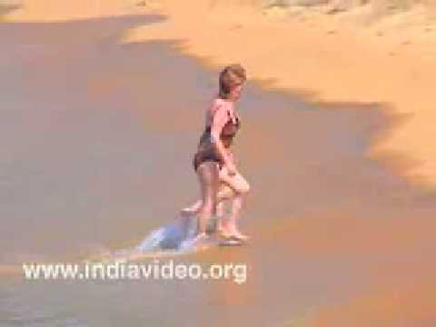 Tourists frolicking in the surf at Kovalam