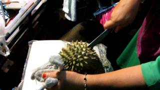 Muslim street stallholder cuts open a Durian fruit in Pedang Besar - Southern Thailand - 720pHD