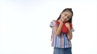 Cute Indian child happily smiling and hugging a red heart-shaped toy - joyful lifestyle