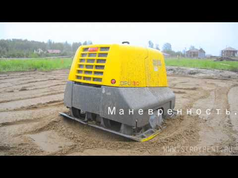Виброплита 1200кг Wacker Neuson DPU130 трамбует песок на строительно площадке.