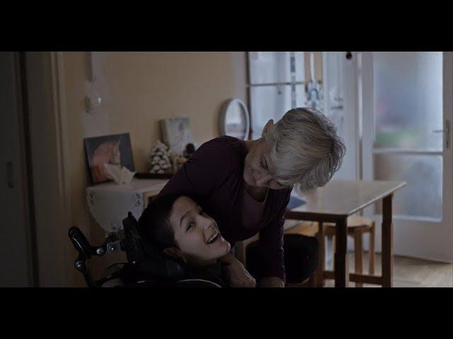 Anya kerekesszékben ülő otthonápolt kislányára néz, lány mosolyog