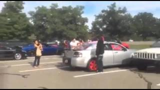 """Guy pulls off """"White Power"""" sticker on car at car show."""