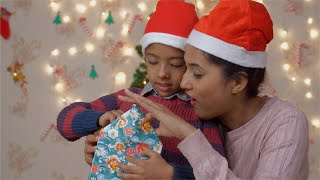 Young Indian mother helping her son in opening Christmas gift