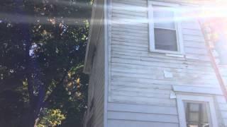 Beginning of facade restoration starts with removal of vinyl siding