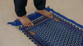 Closeup shot of a young Muslim man's feet standing on a prayer mat in India