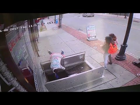 Woman distracted by phone falls into open sidewalk doors