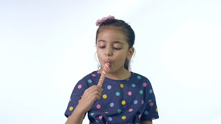 Beautiful Indian girl happily eating a colorful lollipop isolated over white background