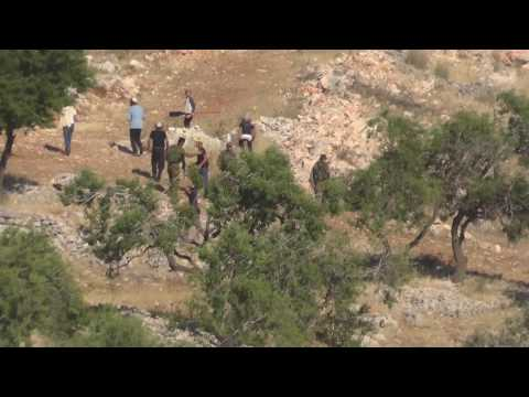 Settlers throw stones at Palestinians as Israeli soldiers stand by in the West Bank