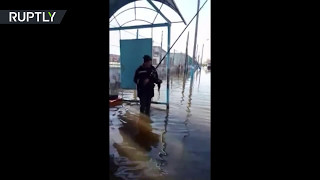 Nothing to see here, just 2 men fishing at flooded bus stop in Kazakhstan