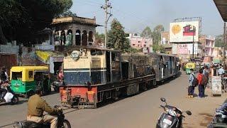 Narrow gauge train on road crossing of Gwalior light railway in Ghosipura India kereta api EIN079460