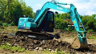 Gambar cover Mini Excavator Kobelco SK75 Spreading The Rocks And Dirt