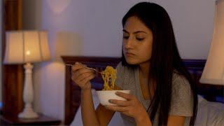 Indian young woman eating instant noodles at home - Unhealthy lifestyle and eating habits
