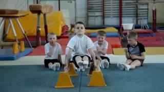 Выполнение упражнений на брусьях. Детская гимнастика. Минск.