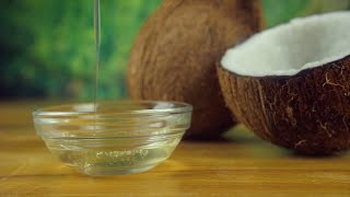 Pouring natural coconut oil into a glass bowl placed on a wooden platform