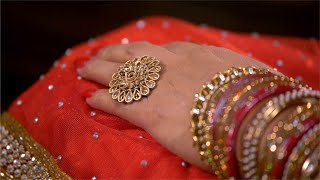 Close shot of women wedding dress with red bangles and golden finger ring