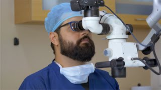 Stock video of a dentist using the microscope to treat his patient in the modern dental office