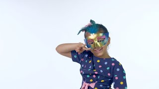 Young Indian kid dancing against the white background in a carnival mask