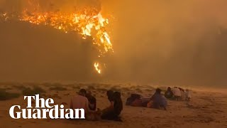 Residents and visitors in NSW town of Rosedale seek refuge from bushfires on the beach