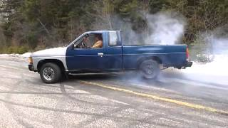 Nissan pickup blowing the rear end in a burnout.