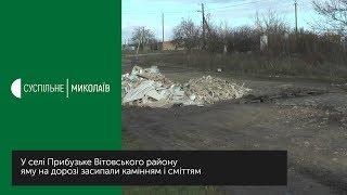 Яму на дорозі засипали камінням і сміттям
