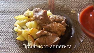 Жареная в луке и чесноке свинина с томатным соусом и гарниром из запеченной картошки.