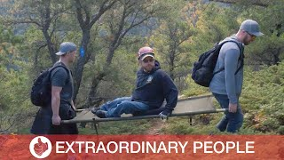 Friends Carry Pal In Wheelchair Up Mountain