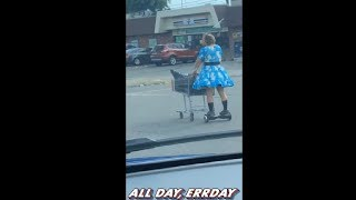 Grown Man In A Dress Pushing A Cart On A Hoverboard In Traffic