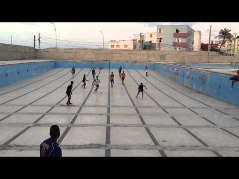 Group of young men playing football inside an empty swimming pool in Havana, Cuba